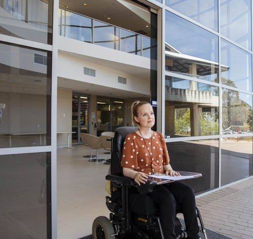 Woman in wheelchair using an accessible automatic door
